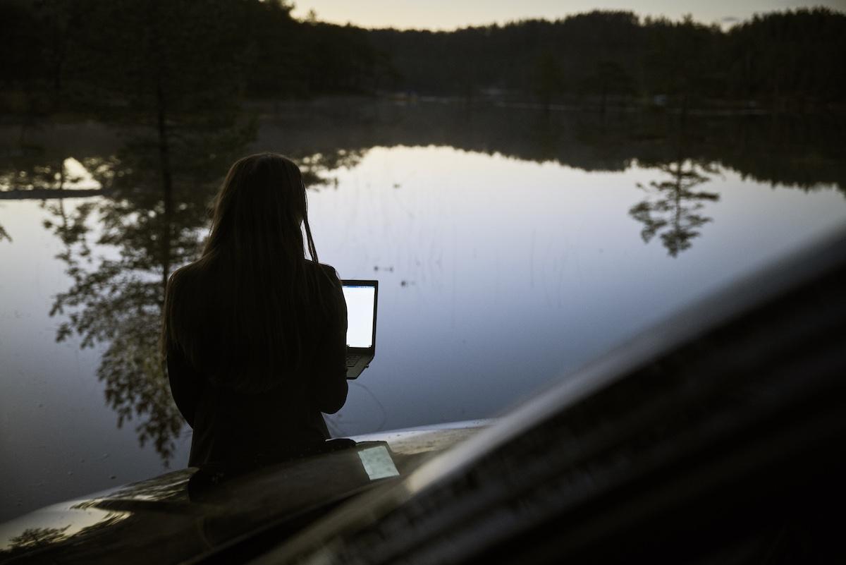 Kvinna med dator vid vatten